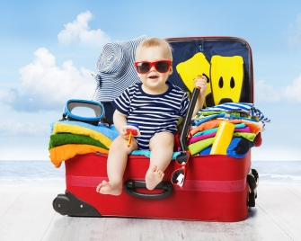 Baby in Travel Suitcase. Kid inside Luggage Packed for Vacation Full of Clothes Child and Family Trip